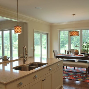 Mid-sized transitional eat-in kitchen pictures - Mid-sized transitional l-shaped medium tone wood floor eat-in kitchen photo in New York with an undermount sink, flat-panel cabinets, white cabinets, quartz countertops, gray backsplash, ceramic backsplash, paneled appliances and an island
