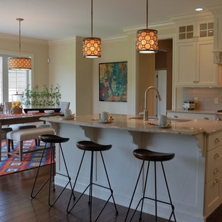 Mid-sized transitional eat-in kitchen designs - Example of a mid-sized transitional l-shaped medium tone wood floor eat-in kitchen design in New York with an undermount sink, flat-panel cabinets, white cabinets, quartz countertops, gray backsplash, ceramic backsplash, paneled appliances and an island