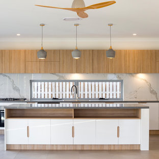 This is an example of a contemporary galley kitchen in Brisbane with flat-panel cabinets, white cabinets, stone slab splashback, stainless steel appliances, with island, beige floor and grey benchtop.