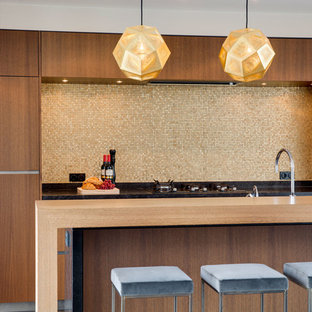 Contemporary open concept kitchen inspiration - Example of a trendy galley open concept kitchen design in Amsterdam with flat-panel cabinets, medium tone wood cabinets, wood countertops, beige backsplash and an island