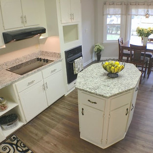 Photo of a mid-sized traditional u-shaped eat-in kitchen in San Diego with an undermount sink, flat-panel cabinets, yellow cabinets, granite benchtops, white splashback, black appliances, vinyl floors and with island.