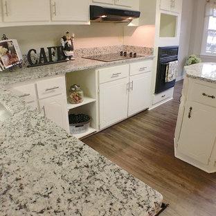 Foto på ett mellanstort vintage kök, med en undermonterad diskho, släta luckor, gula skåp, granitbänkskiva, vitt stänkskydd, svarta vitvaror, vinylgolv och en köksö