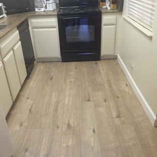 Geschlossene, Einzeilige, Kleine Moderne Küche ohne Insel mit flächenbündigen Schrankfronten, weißen Schränken, Granit-Arbeitsplatte, schwarzen Elektrogeräten und Vinylboden in Sacramento