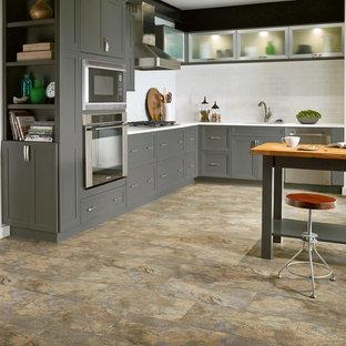 Idéer för att renovera ett mellanstort vintage kök, med luckor med infälld panel, grå skåp, vitt stänkskydd, stänkskydd i tunnelbanekakel, rostfria vitvaror, vinylgolv och en köksö