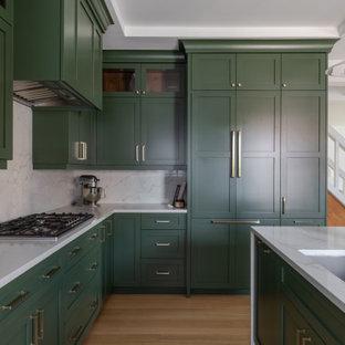 デトロイトの広いトランジショナルスタイルのおしゃれなキッチン (アンダーカウンターシンク、シェーカースタイル扉のキャビネット、緑のキャビネット、クオーツストーンカウンター、白いキッチンパネル、クオーツストーンのキッチンパネル、シルバーの調理設備、淡色無垢フローリング、茶色い床、白いキッチンカウンター、折り上げ天井) の写真