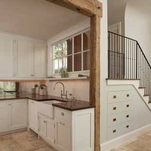 Mid-sized mountain style l-shaped travertine floor and beige floor eat-in kitchen photo in New York with a farmhouse sink, flat-panel cabinets, white backsplash, ceramic backsplash and white cabinets