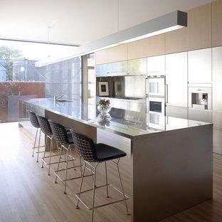 シカゴの小さいモダンスタイルのおしゃれなキッチン (アンダーカウンターシンク、フラットパネル扉のキャビネット、ステンレスキャビネット、ステンレスカウンター、メタリックのキッチンパネル、シルバーの調理設備の、淡色無垢フローリング) の写真