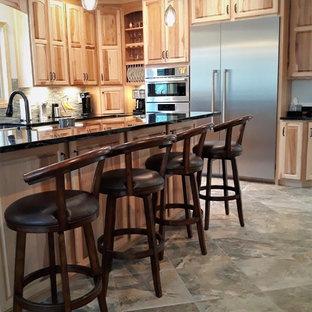 ボストンの巨大なカントリー風おしゃれなキッチン (レイズドパネル扉のキャビネット、淡色木目調キャビネット、大理石カウンター、緑のキッチンカウンター、エプロンフロントシンク、ベージュキッチンパネル、セラミックタイルのキッチンパネル、シルバーの調理設備の、磁器タイルの床、ベージュの床) の写真