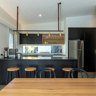 Small contemporary galley eat-in kitchen in Canberra - Queanbeyan with a drop-in sink, raised-panel cabinets, black cabinets, quartz benchtops, window splashback, stainless steel appliances, concrete floors, with island, grey floor and black benchtop.