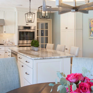 Large transitional eat-in kitchen ideas - Eat-in kitchen - large transitional l-shaped light wood floor eat-in kitchen idea in Boston with an undermount sink, shaker cabinets, white cabinets, granite countertops, green backsplash, glass tile backsplash, stainless steel appliances and an island