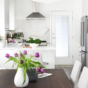 Bild på ett litet funkis vit vitt kök, med en undermonterad diskho, släta luckor, vita skåp, bänkskiva i kvarts, vitt stänkskydd, rostfria vitvaror, laminatgolv och grått golv