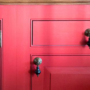 Mittelgroße Landhaus Wohnküche mit Landhausspüle, roten Schränken, Speckstein-Arbeitsplatte, Küchengeräten aus Edelstahl, hellem Holzboden, Kücheninsel, Kassettenfronten, Küchenrückwand in Schwarz und Rückwand aus Stein in Boston