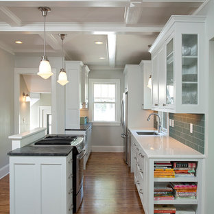 Inspiration for a small arts and crafts galley open plan kitchen in Minneapolis with a single-bowl sink, recessed-panel cabinets, grey cabinets, soapstone benchtops, green splashback, glass tile splashback, stainless steel appliances, medium hardwood floors, with island and beige floor.