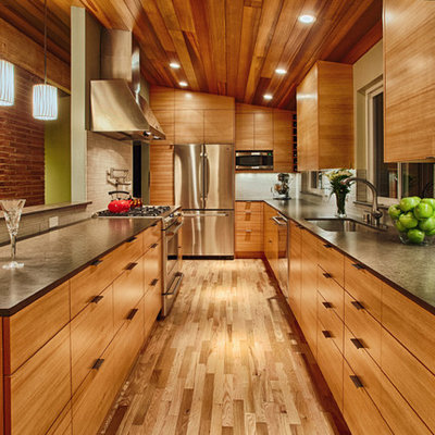Mid-sized trendy galley medium tone wood floor and brown floor open concept kitchen photo in Seattle with flat-panel cabinets, medium tone wood cabinets, gray backsplash, stainless steel appliances, an undermount sink, quartz countertops and porcelain backsplash