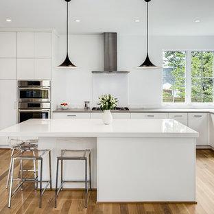 Foto på ett mellanstort funkis kök, med en undermonterad diskho, släta luckor, vita skåp, bänkskiva i kvartsit, rostfria vitvaror, ljust trägolv, en köksö och beiget golv