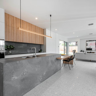 Design ideas for a contemporary galley open plan kitchen in Canberra - Queanbeyan with a double-bowl sink, flat-panel cabinets, white cabinets, grey splashback, stone slab splashback, stainless steel appliances, with island, grey benchtop and grey floor.
