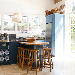 This is an example of a medium sized farmhouse kitchen in Kent with blue cabinets, shaker cabinets, black splashback, stainless steel appliances, beige floors and black worktops.