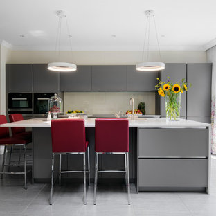 Design ideas for a medium sized contemporary kitchen in London with flat-panel cabinets, grey cabinets, composite countertops, beige splashback, glass sheet splashback, cement flooring, an island and grey floors.