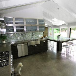 Modern inredning av ett kök, med en rustik diskho, luckor med glaspanel, skåp i rostfritt stål, bänkskiva i kvarts, blått stänkskydd, glaspanel som stänkskydd, rostfria vitvaror, betonggolv och en köksö