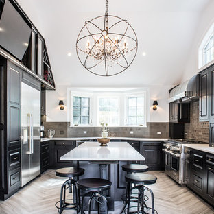 This is an example of a large transitional u-shaped eat-in kitchen in New York with black cabinets, stainless steel appliances, with island, raised-panel cabinets, an undermount sink, solid surface benchtops, grey splashback, ceramic splashback and porcelain floors.