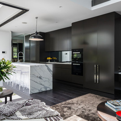 Inspiration for a mid-sized contemporary galley dark wood floor and brown floor open concept kitchen remodel in Sydney with an undermount sink, marble countertops, mirror backsplash, black appliances, an island, white countertops, flat-panel cabinets and black cabinets