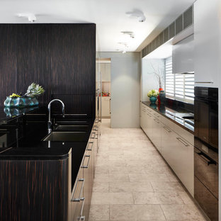 This is an example of a contemporary galley kitchen in Sydney with an undermount sink, flat-panel cabinets, dark wood cabinets, a peninsula, beige floor, black benchtop, marble benchtops, black splashback, stone slab splashback, black appliances and limestone floors.