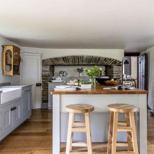 Photo of a medium sized rural l-shaped kitchen in Devon with a belfast sink, grey cabinets, granite worktops, an island, beige floors, grey worktops, shaker cabinets and medium hardwood flooring.