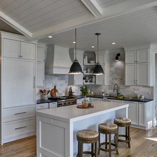 Foto på ett mellanstort maritimt vit kök, med en undermonterad diskho, släta luckor, vita skåp, bänkskiva i kvartsit, grått stänkskydd, stänkskydd i marmor, integrerade vitvaror, ljust trägolv, en köksö och flerfärgat golv