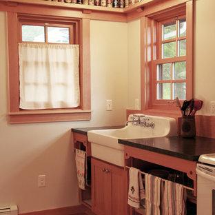 Идея дизайна: маленькая прямая кухня-гостиная в классическом стиле с раковиной в стиле кантри, открытыми фасадами, фасадами цвета дерева среднего тона, столешницей из акрилового камня, коричневым фартуком, белой техникой, полом из бамбука и коричневым полом без острова
