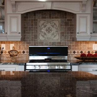 トロントの大きいヴィクトリアン調のおしゃれなキッチン (アンダーカウンターシンク、レイズドパネル扉のキャビネット、白いキャビネット、御影石カウンター、ベージュキッチンパネル、セラミックタイルのキッチンパネル、シルバーの調理設備の) の写真