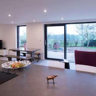 This is an example of a contemporary galley eat-in kitchen in Manchester with an integrated sink, flat-panel cabinets, black cabinets, laminate benchtops, stainless steel appliances, ceramic floors and with island.