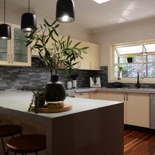 Design ideas for a mid-sized contemporary u-shaped eat-in kitchen in Melbourne with a double-bowl sink, yellow cabinets, quartz benchtops, grey splashback, slate splashback, stainless steel appliances, with island and grey benchtop.