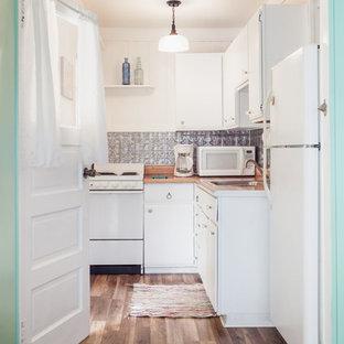 タンパの小さいビーチスタイルのおしゃれなII型キッチン (ドロップインシンク、フラットパネル扉のキャビネット、ラミネートカウンター、メタリックのキッチンパネル、メタルタイルのキッチンパネル、白い調理設備、クッションフロア) の写真