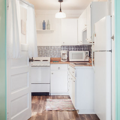 Small beach style galley vinyl floor kitchen photo in Tampa with a drop-in sink, flat-panel cabinets, laminate countertops, metallic backsplash, metal backsplash and white appliances