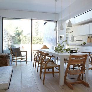 Modelo de cocina comedor lineal, nórdica, con armarios con paneles lisos, puertas de armario blancas, salpicadero blanco y suelo de madera clara