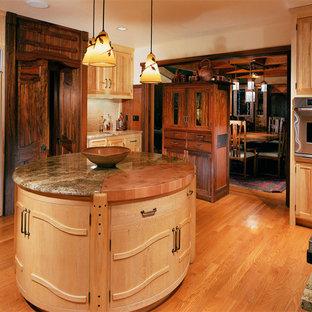 Inspiration pour une grand cuisine ouverte craftsman en U avec un évier encastré, un placard à porte plane, des portes de placard en bois clair, un plan de travail en granite, une crédence en carrelage de pierre, un électroménager encastrable, un sol en bois brun et un îlot central.