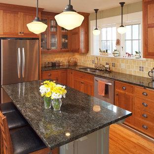 ミネアポリスのトラディショナルスタイルのおしゃれなL型キッチン (ダブルシンク、シェーカースタイル扉のキャビネット、中間色木目調キャビネット、黄色いキッチンパネル、シルバーの調理設備) の写真