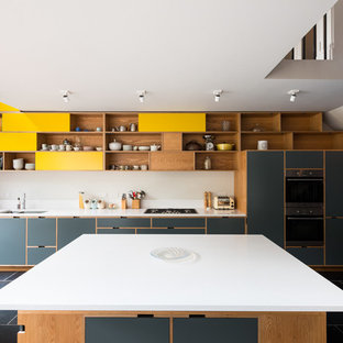 Photo of a contemporary kitchen/diner in London with medium wood cabinets, engineered stone countertops, white splashback, integrated appliances, slate flooring and an island.