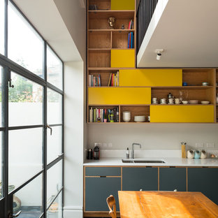 This is an example of a contemporary eat-in kitchen in London with medium wood cabinets, white splashback, slate floors, a double-bowl sink and open cabinets.