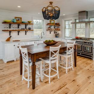 Mittelgroße Maritime Wohnküche in U-Form mit Rückwand-Fenster, schwarzen Elektrogeräten, hellem Holzboden, Kücheninsel, beigem Boden, Landhausspüle, Kassettenfronten, weißen Schränken, Marmor-Arbeitsplatte und Küchenrückwand in Weiß in Sonstige