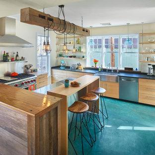 Inspiration för ett mellanstort eklektiskt kök, med en rustik diskho, släta luckor, skåp i ljust trä, bänkskiva i rostfritt stål, rostfria vitvaror, betonggolv, en köksö och turkost golv