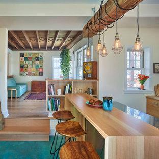 Mittelgroße Stilmix Wohnküche in L-Form mit Landhausspüle, flächenbündigen Schrankfronten, hellen Holzschränken, Edelstahl-Arbeitsplatte, Küchengeräten aus Edelstahl, Betonboden, Kücheninsel und türkisem Boden in Philadelphia