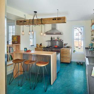 Inredning av ett eklektiskt mellanstort kök, med en rustik diskho, släta luckor, skåp i ljust trä, bänkskiva i rostfritt stål, rostfria vitvaror, betonggolv, en köksö och turkost golv
