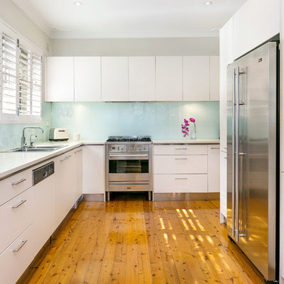 Enclosed kitchen - mid-sized contemporary l-shaped medium tone wood floor enclosed kitchen idea in Sydney with a double-bowl sink, white cabinets, limestone countertops, glass sheet backsplash, stainless steel appliances, flat-panel cabinets and blue backsplash