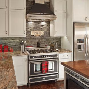 Mittelgroße Klassische Küche in U-Form mit Schrankfronten mit vertiefter Füllung, weißen Schränken, Küchenrückwand in Grau, schwarzen Elektrogeräten, dunklem Holzboden, Rückwand aus Schiefer, Granit-Arbeitsplatte, Kücheninsel und braunem Boden in Dallas