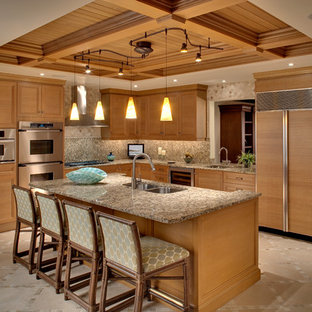 Tropical u-shaped eat-in kitchen in Miami with a double-bowl sink, recessed-panel cabinets, medium wood cabinets, multi-coloured splashback, panelled appliances, granite benchtops, stone slab splashback, porcelain floors and with island.