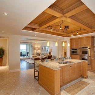 Idee per una grande cucina tropicale con lavello sottopiano, ante a persiana, ante in legno chiaro, top in granito, paraspruzzi marrone, elettrodomestici in acciaio inossidabile e isola