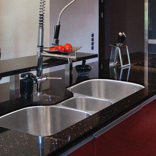 ニューヨークの大きいコンテンポラリースタイルのおしゃれなキッチン (アンダーカウンターシンク、フラットパネル扉のキャビネット、赤いキャビネット、再生ガラスカウンター、黒いキッチンパネル、シルバーの調理設備の、リノリウムの床) の写真