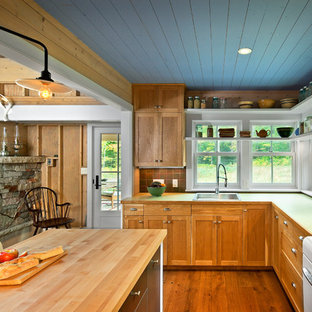 Open concept kitchen - mid-sized country l-shaped medium tone wood floor open concept kitchen idea in Minneapolis with a drop-in sink, shaker cabinets, medium tone wood cabinets, wood countertops, brown backsplash, white appliances and an island