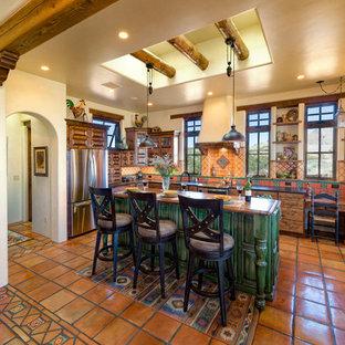 Exemple d'une cuisine sud-ouest américain en L avec un placard avec porte à panneau surélevé, des portes de placard en bois sombre, une crédence multicolore, un électroménager en acier inoxydable, un îlot central et un sol orange.